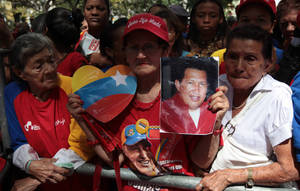 "Photo - A woman holds a picture of Venezuela's President Hugo Chavez as supporters gather at Simon Bolivar square in Caracas,Venezuela, Sunday Dec.  9, 2012.  Chavez is to return to Cuba Sunday for another surgery in his battle against cancer, which has led him to speak publicly of a successor for the first time.  Chavez said Saturday that if there are ""circumstances that prevent me from exercising the presidency further""  Vice-President Nicolas Maduro should replace him for the remainder of his term.(AP Photo/Fernando Llano)"