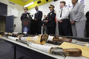 Photo - FILE - In this Jan. 28, 2013, file photo, Chicago Police First Deputy Superintendent Alfonsa Wysinger, second from left, speaks at a news conference in Chicago with a display of recently seized guns, part of the 574 that had been seized in the city since Jan. 1. The mounting homicide toll in President Barack Obama's hometown has giving ammunition to both sides in the nation's debate about gun rights and safety. On Monday, Jan. 6, 2014, a federal judge in Chicago potentially opened a new market to gun dealers after ruling as unconstitutional Chicago ordinances that aim to reduce gun violence by banning their sale within the city's limits. (AP Photo/M. Spencer Green, File)