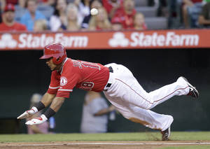 Photo - Los Angeles Angels' Luis Jimenez slides into home plate to score on a sacrifice fly by Grant Green during the second inning of a baseball game against the Texas Rangers on Saturday, Sept. 7, 2013, in Anaheim, Calif. (AP Photo/Jae C. Hong)