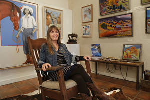 Photo - Cynthia Wolf, owner of Adelante! Gallery sits in front of paintings by Donna Howell-Sickle, left, and Leigh Gusterson, Friday, November 22, 2013, at the gallery. Photo by Doug Hoke, The Oklahoman <strong>DOUG HOKE - THE OKLAHOMAN</strong>