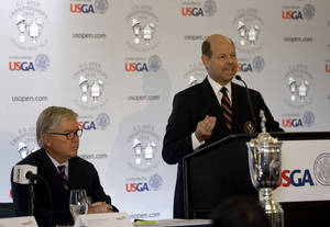 Photo - Mike Davis, right, Executive Director of the United States Golf Association, speaks as USGA President Thomas J. O'Toole, left, listens at Pinehurst Resort & Country Club during media day for the upcoming back-to-back U.S. Open and U.S. Women's Open golf championships to be held this June in Pinehurst, N.C., Monday, April 21, 2014. (AP Photo/Gerry Broome)