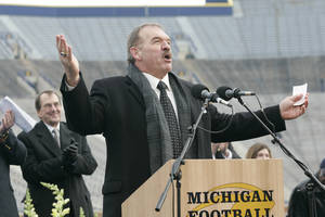 Photo - FILe - In this Nov. 21, 2006 file photo, former Michigan football player Dan Dierdorf speaks at a public memorial service for former Michigan football coach Bo Schembechler, with Michigan head coach Lloyd Carr behind him on stage, at Michigan Stadium in Ann Arbor, Mich. Dierdorf is coming back to the booth and will be the radio analyst for University of Michigan football games this fall. The announcement Thursday, April 17, 2014,  was made by Michigan and IMG College, the school's multimedia rights partner. (AP Photo/Tony Ding, File)