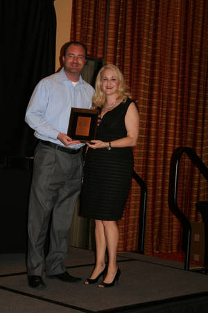 Photo -  John Woods, Norman Chamber of Commerce, accepts award from Paisley Hopkins of the Yukon Chamber of Commerce. (Photo provided)