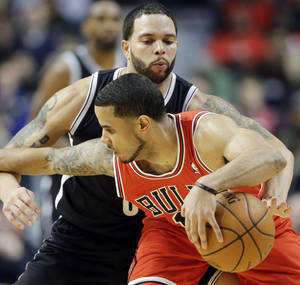 Photo - Brooklyn Nets guard Deron Williams, behind, tries to steal the ball from Chicago Bulls guard D.J. Augustin during the first half of an NBA basketball game in Chicago on Thursday, Feb. 13, 2014. (AP Photo/Nam Y. Huh)