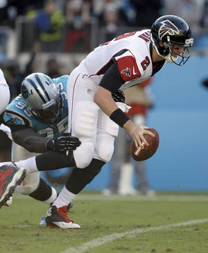 Photo - Atlanta Falcons' Matt Ryan (2) tries to get away from Carolina Panthers' Charles Johnson (95) in the second half of an NFL football game in Charlotte, N.C., Sunday, Nov. 3, 2013. (AP Photo/Bob Leverone)
