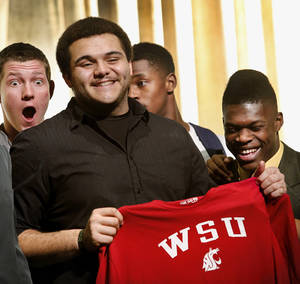 Photo - Midwest City High School offensive lineman Carlos Freeman holds a jersey while posing with fellow members of his team after signing his name to a letter of intent to play football at Washington State University during a ceremony in the school's performing arts building on Wednesday, Feb. 6, 2013.   Photo by Jim Beckel, The Oklahoman