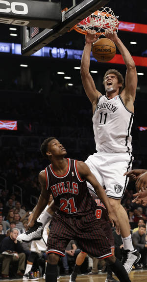 photo - Brooklyn Nets center Brook Lopez, top, dunks over Chicago Bulls forward Jimmy Butler (21) in the first half of an NBA basketball game at the Barclays Center, Friday, Feb. 1, 2013,in New York. (AP Photo/Kathy Willens)