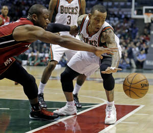 Photo - Milwaukee Bucks' Monta Ellis, right, and Miami Heat's Dwyane Wade battle for a loose ball during the first half of Game 3 in their first-round NBA basketball playoff series on Thursday, April 25, 2013, in Milwaukee. (AP Photo/Morry Gash)