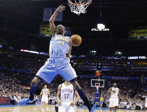 Photo -   Denver Nuggets forward Corey Brewer dunks in front of Oklahoma City Thunder guard Derek Fisher (37) during the first quarter of an NBA basketball game in Oklahoma City, Wednesday, April 25, 2012. (AP Photo/Sue Ogrocki)