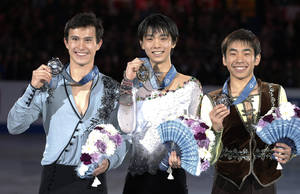 Photo - FILE - In this Friday, Dec. 6, 2013 file photo, winner Yuzuru Hanyu, center, of Japan, second-placed Patrick Chan, right, of Canada and third-placed Nobunari Oda of Japan pose for photographers after the awarding ceremony of men's event of the ISU Grand Prix Final figure skating in Fukuoka, western Japan. Hanyu's decision to shift his training base to Canada was just what the Japanese teenager needed to become a contender for the gold medal in men's figure skating at the Sochi Olympics. Moving to Toronto to train under renowned coach Brian Orser has already paid off for the 19-year-old Hanyu, who beat three-time world champion Chan at the International Skating Union's Grand Prix final in December. (AP Photo/Shizuo Kambayashi, File)