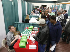 Photo - In this April 22, 2014 photo, Bryan Preston of Hannaford supermarkets, left, talks with job seekers during a job fair at Columbia-Greene Community College in Hudson, N.Y. The Labor Department reports the number of people who applied for unemployment benefits last week on Thursday, May 8, 2014. (AP Photo/Mike Groll)
