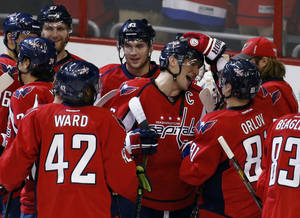 Photo - Washington Capitals right wing Alex Ovechkin (8), from Russia, center, celebrates with his teammates including right wing Joel Ward (42) and defenseman Dmitry Orlov (81), from Russia, after an NHL hockey game against the Philadelphia Flyers, Sunday, Dec. 15, 2013, in Washington. The Capitals won 5-4 in a shootout. (AP Photo/Alex Brandon)