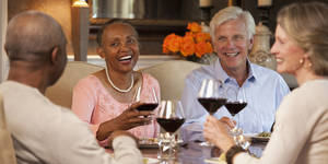 Photo - Smiling couples toasting wine glasses at dining room table
