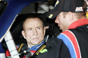 Photo - Driver Mark Martin, left, talks with a crew member before the start of practice for Sunday's NASCAR Sprint Cup Dickies 500 auto race at Texas Motor Speedway on Saturday. Martin is enjoying this season, competing well in the Sprint Cup at age 50.  AP PHOTO
