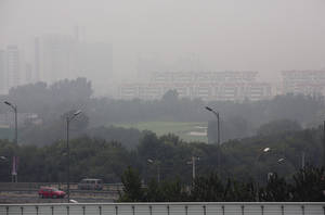 Photo - Vehicles drive past residential apartment buildings shrouded by haze in Beijing, China Sunday, Oct. 6, 2013. Fog and pollution descended on northern China on Sunday, leading to flight cancellations and road closures at a time when millions of Chinese were headed home as a weeklong national holiday neared its end. (AP Photo/Andy Wong)