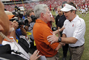 photo - Bob Stoops and Mack Brown meet at mid field after the Sooners' 63-21 win over Texas during the Red River Rivalry college football game between the University of Oklahoma (OU) and the University of Texas (UT) at the Cotton Bowl in Dallas, Saturday, Oct. 13, 2012. Photo by Chris Landsberger, The Oklahoman