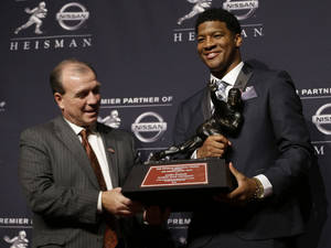 Photo - Florida State quarterback Jameis Winston, right, stands with FSU coach Jimbo Fisher while holding the Heisman Trophy after winning the award on Saturday, Dec. 14, 2013, in New York. (AP Photo/Julio Cortez)