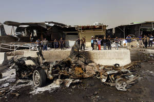 photo - Iraqis inspect the scene of a car bomb attack in the Ameen neighborhood of eastern Baghdad, Iraq, Sunday, Feb. 17, 2013. A series of car bombs exploded within minutes of each other as Iraqis were out shopping in and around Baghdad on Sunday, killing and wounding scores of people, police said. (AP Photo/ Khalid Mohammed)