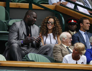 Photo - US retired basketball player Shaquille O'Neal, left, talks to an unidentified woman as he watches a match on the centre court  during the first day at the All England Lawn Tennis Championships in Wimbledon, London,  Monday, June  23, 2014. (AP Photo/Pavel Golovkin)