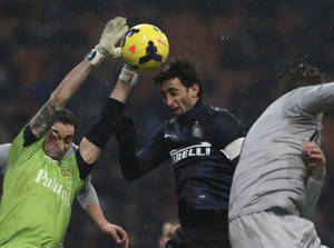 Photo - Chievo goalie Christian Puggioni, left, saves on a header of Inter Milan Argentine forward Diego Milito during a Serie A soccer match between Inter Milan and Chievo Verona, at the San Siro stadium in Milan, Italy, Monday, Jan.13, 2014. (AP Photo/Luca Bruno)