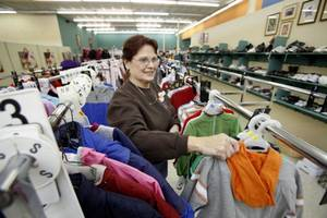 Photo - Volunteer Della Decker hangs children's coats at the Christmas Connection store in southwest Oklahoma City on Thursday. <strong>Steve Gooch - The Oklahoman</strong>