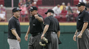 Photo -   South Carolina coach Ray Tanner, left, talks to the umpires after his runner was sent back to second base in the eighth inning of an NCAA college baseball tournament super regional game against Oklahoma in Columbia, S.C., Monday, June 11, 2012. (AP Photo/Mary Ann Chastain)