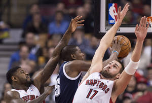 Photo - Toronto Raptors forward Amir Johnson, left, and Jonas Valanciunas, right, defend against Oklahoma Thunder forward Kevin Durant, center, during the first half of an NBA basketball game in Toronto on Friday, March 21, 2014. (AP Photo/The Canadian Press, Nathan Denette)
