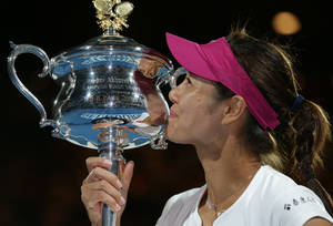 Photo - Li Na of China kisses the championship trophy after defeating Dominika Cibulkova of Slovakia in their women's singles final at the Australian Open tennis championship in Melbourne, Australia, Saturday, Jan. 25, 2014.(AP Photo/Aaron Favila)