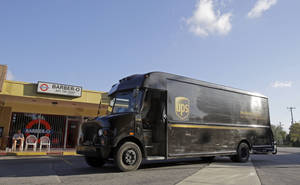 Photo - In this  Monday, Jan. 28, 2013, photo, a UPS truck arrives for a delivery Miami Springs, Fla. United Parcel Service Inc. says it was slowed down in the fourth quarter  of 2012, by weak global trade and a disappointing holiday-shopping season.  (AP Photo/Alan Diaz)