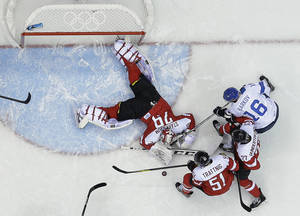 Photo - Austria goaltender Bernhard Starkbaum reaches for the rebound as Finland forward Aleksander Barkov looks to score in the third period of a men's ice hockey game at the 2014 Winter Olympics, Thursday, Feb. 13, 2014, in Sochi, Russia. (AP Photo/Mark Humphrey )