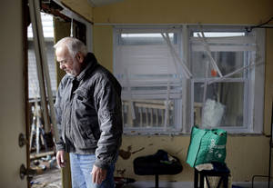 Photo - Chuck Clauser looks out from a hole where a wall once stood at his home, damaged by a surge from Superstorm Sandy on Cedar Bonnet Island, N.J. (AP Photo/Patrick Semansky) ORG XMIT: NJPS115