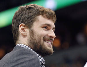 Photo - Minnesota Timberwolves forward Kevin Love smiles as he did not play in the game against the Portland Trail Blazers on Saturday, February 8, 2014 in Minneapolis.(AP Photo/Andy Clayton-King)