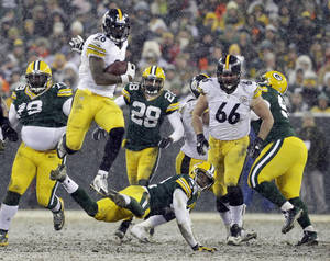 Photo - Pittsburgh Steelers' Le'Veon Bell (26) leaps over Green Bay Packers' Morgan Burnett during the second half of an NFL football game Sunday, Dec. 22, 2013, in Green Bay, Wis. (AP Photo/Mike Roemer)