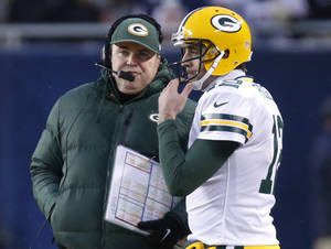 Photo - Green Bay Packers head coach Mike McCarthy talks to quarterback Aaron Rodgers (12) during the first half of an NFL football game against the Chicago Bears, Sunday, Dec. 29, 2013, in Chicago. (AP Photo/Charles Rex Arbogast)