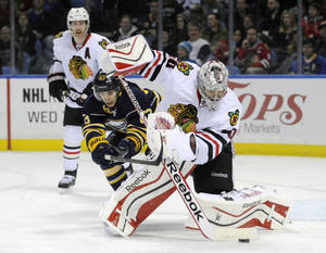 Photo - Buffalo Sabres center Tyler Ennis (63) hooks Chicago Black Hawks goaltender Corey Crawford who handles the puck during the first period of an NHL hockey game in Buffalo, N.Y., Sunday, March 9, 2014. (AP Photo/Gary Wiepert)