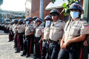 photo - Venezuelan police officers stand guard outside the morgue where the bodies of prisoners killed in a riot were taken in Barquisimeto,Venezuela, Saturday, Jan. 26, 2013. A clash between National Guard soldiers and armed inmates led to a deadly riot Friday that reportedly left dozens of people dead. According to a local hospital director the death toll has risen to 61 and 120 injured. (AP Photo/Misael Castro/El Informador)