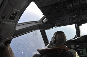 Photo - In this , Tuesday, April 1, 2014 photo made available Thursday, April 3, 2014, a crewman on a Royal New Zealand Air Force P-3 Orion Rescue Flight 795 searches for debris from the missing Malaysia Airlines Flight MH370, in southern Indian Ocean, 1,500 kilometers northwest of Perth, Australia. The focus of the search has changed repeatedly in the nearly four weeks since the air traffic controllers lost contact with the Boeing 777 between Malaysia and Vietnam over the South China Sea. It began in the South China Sea, then shifted toward the Malacca Strait to the west, where Malaysian officials eventually confirmed that military radar had detected the plane. (AP Photo/AAP Image, Kim Christian, POOL)