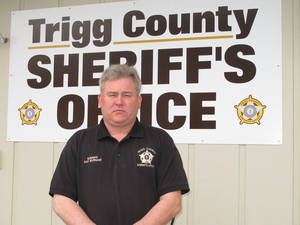 "Photo - In  this Tuesday, Dec. 4, 2012, photo, Trigg County Sheriff Ray Burnam stands in front of the sheriff's department in Cadiz, Ky. When Burnam offered $1,000 of his own money as a reward for information leading to a conviction in three unsolved murder cases in western Kentucky county, law enforcement issued a court order demanding Burnam turn over his findings in one case and claimed he had gone ""rogue"". AP Photo/Bruce Schreine"