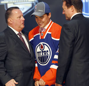 Photo -   Nail Yakupov, center, a winger from Russia who was chosen first overall by the Edmonton Oilers in the first round of the NHL hockey draft, stands with Oilers officials on Friday, June 22, 2012, in Pittsburgh. (AP Photo/Keith Srakocic)
