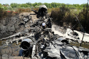 Photo - A National Transportation Safety Board official looks through the wreckage at the scene Monday, June 2, 2014, in Bedford, Mass., where a plane plunged down an embankment and erupted in flames during a takeoff attempt at Hanscom Field Saturday night. Lewis Katz, co-owner of the Philadelphia Inquirer and six other people died in the crash. (AP Photo/Boston Herald, Mark Garfinkel, Pool)