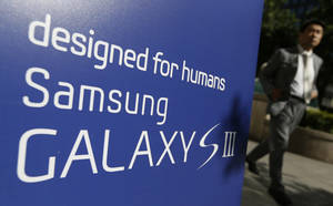 Photo -   A man walks near a banner advertising Samsung's Galaxy S III smartphone in Seoul, South Korea, Thursday, Sept. 6, 2012. Samsung said global sales of its Galaxy S III smartphone have surpassed 20 million in a little more than three months. (AP Photo/Lee Jin-man)