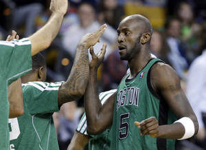 photo - Boston Celtics center Kevin Garnett (5) receives congratulations from teammates as he walks to the bench during the fourth quarter of an NBA basketball game against the Toronto Raptors in Boston, Wednesday, March 13, 2013. Garnett scored 12 points, passing Jerry West for 15th on the NBA's career scoring list. The Celtics won 112-88. (AP Photo/Elise Amendola)