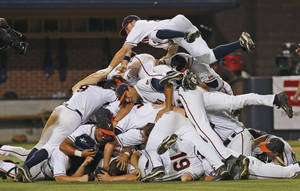 Photo - Virginia players pile on each other to celebrate after Virginia defeated Maryland 11-2 to win the NCAA Super Regional baseball game in Charlottesville, Va., Monday, June 9, 2014. (AP Photo/Steve Helber)