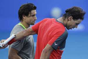 Photo - David Ferrer of Spain, left, and his fellow countryman Rafael Nadal of Spain leave the court after their match during the second day of the Mubadala World Tennis Championship in Abu Dhabi, United Arab Emirates, Friday Dec. 27, 2013. (AP Photo/Kamran Jebreili)