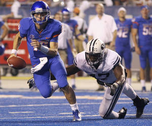 Photo -   Boise State's Joe Southwick scrambles as Bingham Young's Ezekiel Ansah dives for him during an NCAA college football game Thursday, Sept. 20, 2012, in Boise, Idaho. (AP Photo/The Times-News, Drew Nash)
