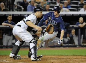 Photo -   Tampa Bay Rays' Elliot Johnson scores at home plate past New York Yankees catcher Russell Martin on an RBI single by Ben Zobrist in the seventh inning of a baseball game on Friday, Sept., 14, 2012, at Yankee Stadium in New York. (AP Photo/Kathy Kmonicek)