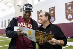 Photo - Florida State Jimbo Fisher, right, looks at a magazine with quarterback Jameis Winston during pro day at Florida State on Tuesday, March 18, 2014, in Tallahassee, Fla. Winston did not participate in pro day, but came by to visit Fisher after the event. (AP Photo/Colin Hackley)