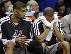 Photo - San Antonio Spurs' Tim Duncan, left, and Tony Parker, right, react against the Golden State Warriors during the second half in Game 2 of a Western Conference semifinal NBA basketball playoff series, Wednesday, May 8, 2013, in San Antonio. Golden State won 100-91.(AP Photo/Eric Gay)