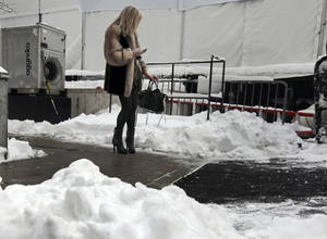photo - A woman checks her mobile phone outside Lincoln Center, home of New York's Fashion Week shows, Saturday, Feb. 9, 2013. In New York City, the snow total in Central Park was 8.1 inches by 3 a.m. (AP Photo/Richard Drew)