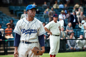 """Photo - This film image released by Warner Bros. Pictures shows Chadwick Boseman as Jackie Robinson in a scene from """"42."""" Kansas City's Negro Leagues Baseball Museum is hosting an advance screening of an upcoming movie about Jackie Robinson, who broke major league baseball's color barrier. Thomas Butch of the financial firm Waddell and Reed announced Wednesday, March 20, 2013, that actors Harrison Ford and Andre Holland will be among those appearing at an April 11 screening of """"42.""""  The film chronicles Robinson's rise from the Negro Leagues' Kansas City Monarchs in 1945 to the Brooklyn Dodgers in 1947, when he won the inaugural Rookie of the Year award. The film opens nationwide on April 12. (AP Photo/Warner Bros. Pictures, D. Stevens)"""